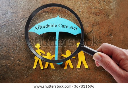Paper family under a Affordable Care Act umbrella with magnifying glass                              - stock photo