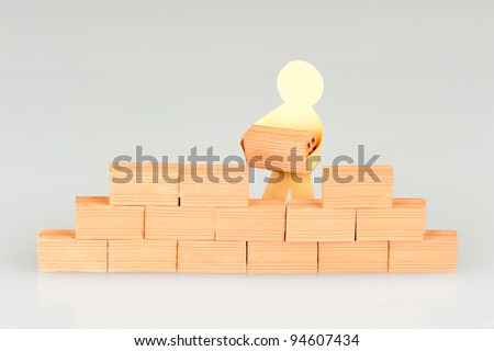 paper figure building a wall - stock photo