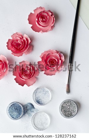 Paper flowers for creativity. Placing glitter on the pink paper flowers - stock photo