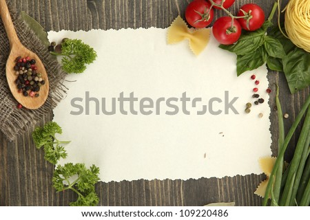 paper for recipes vegetables, and spices on wooden table - stock photo