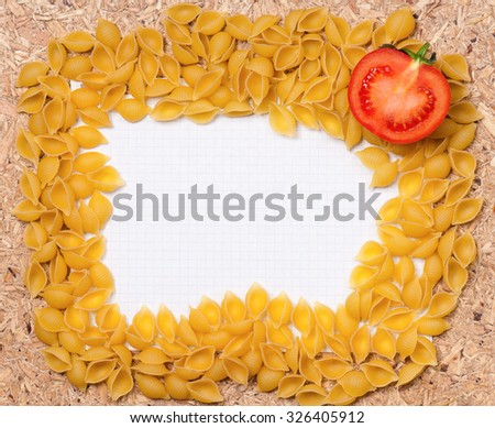 Paper for recipes with pasta and tomato on wooden table - stock photo