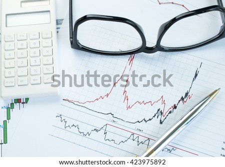 Paper graph with pen ,calculator and eyeglasses stock market analysis - stock photo