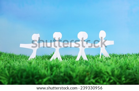 Paper group of people holding hands on green grass on blue background