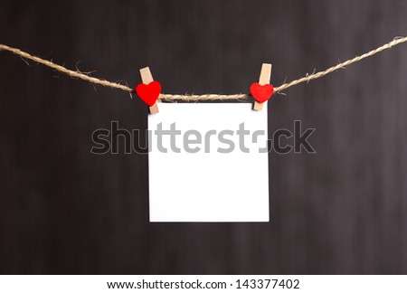 paper hang on clothesline with clothes pins, with red heart, on dark grey background