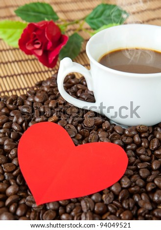 paper heart and coffee on coffee beans