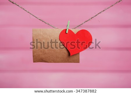 Paper hearts and empty sheet hanging on cord against pink wooden background - stock photo