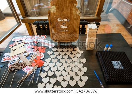 Paper hearts and sticks with letterings lie on table