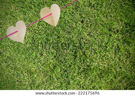 Paper hearts on green grass - stock photo