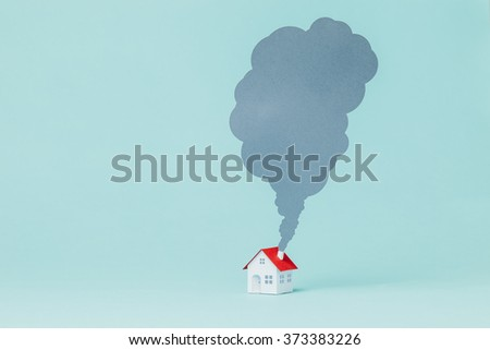 Paper house and chimney smoke. - stock photo