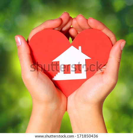 Paper House and Heart in Female Hands over Nature Green Sunny Background. Concept