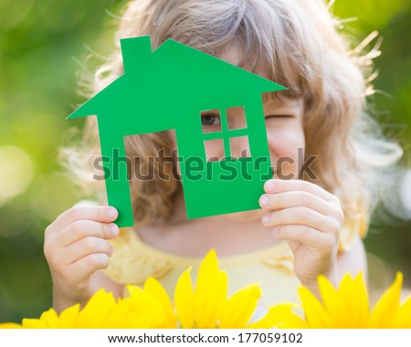 Paper house in hand against spring green background. Real estate concept - stock photo