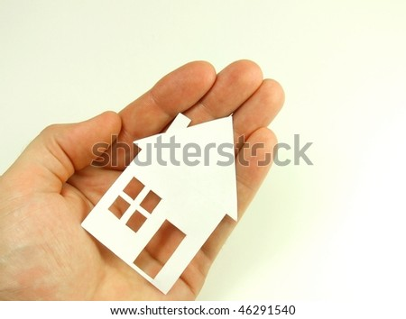 Paper house on human hand concept - stock photo