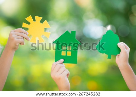 Paper house, tree and sun in hands against spring green blurred background. Ecology concept - stock photo