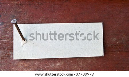 Paper label attached on wood wall with nail. - stock photo