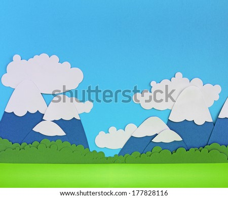 Paper landscape with mountains, trees, clouds and meadow - stock photo