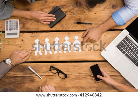 Paper man chain holding hands. Teamwork concept with paper chain, group of people holding hands held over wooden table. Businesspeople holding paper man chain depicting unity and team work. - stock photo