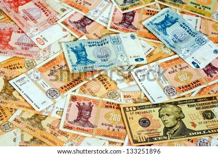paper money of different denominations and different countries spread out on the table.