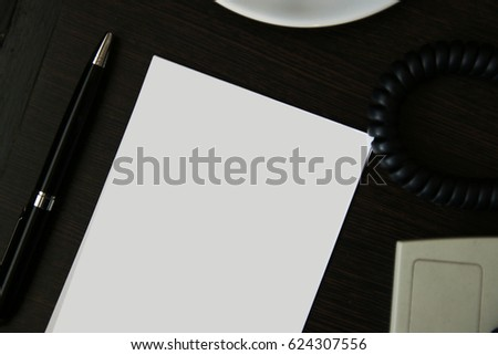 paper note and phone on wood table