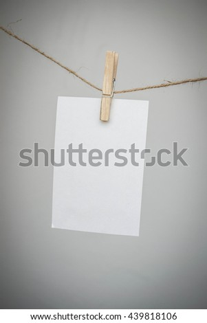 paper note hanging on a rope clamp with a clothes peg - stock photo