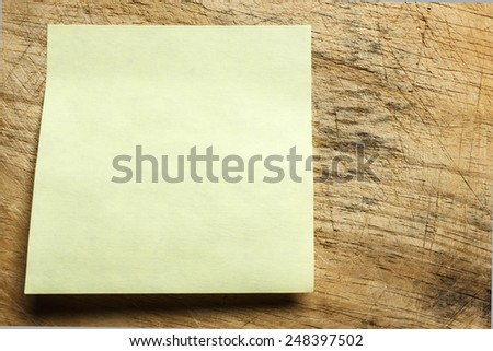 Paper note on wooden background. - stock photo