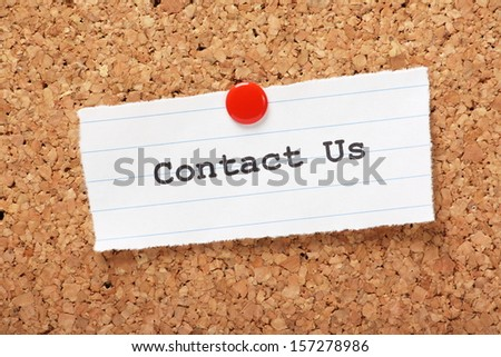 Paper note pinned to a cork notice board with the phrase Contact Us typed onto it - stock photo