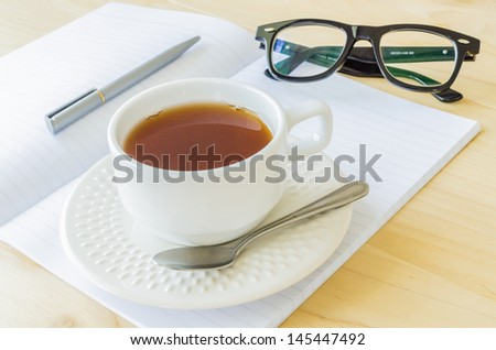 Paper note with eye glasses&white cuptea - stock photo