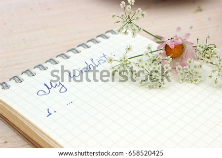 Paper notebook with handwritten text: My Wishlist. Concept for romantic and love theme