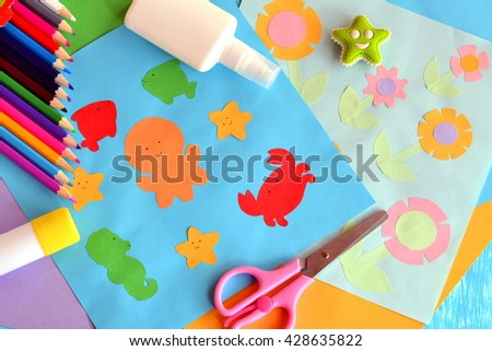 Paper octopus, fish, starfish, crab, flowers. Project idea using a colored paper. Applique work for children. Crafts from colored paper. Glue, scissors, pencils, eraser. Funny background  - stock photo