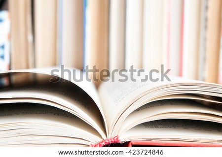Paper pages of a book folded  on the background of a series of old books - stock photo