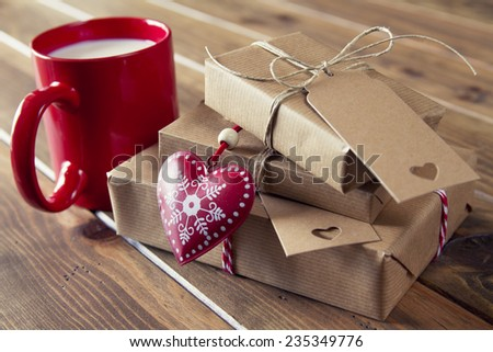 Paper parcels wrapped tied with tags. A milk mug for Santa, a heart and some  christmas gift boxes wrapped with paper kraft and tied with red & white baker's twine on a wooden table. Vintage Style - stock photo