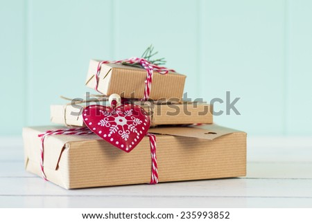 Paper parcels wrapped tied with tags. A red heart and some christmas gift boxes wrapped with paper kraft and tied with red & white baker's twine on a white table with a turquoise wainscot. Vintage - stock photo