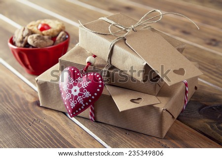 Paper parcels wrapped tied with tags. Cookies in a bowl, a red heart and some christmas gift boxes wrapped with paper kraft and tied with red & white baker's twine on a wooden table. Vintage Style. - stock photo