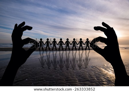 Paper people in  man hand over sunset of silhouette - stock photo