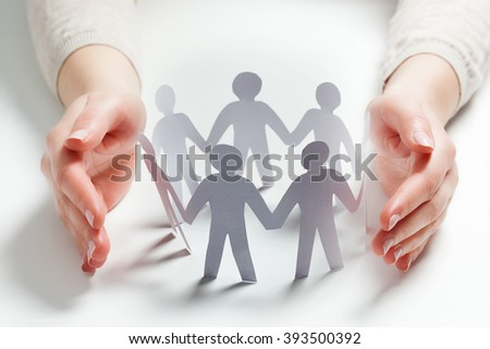 Paper people surrounded by hands in gesture of protection. Concept of insurance, social protection and support.  - stock photo