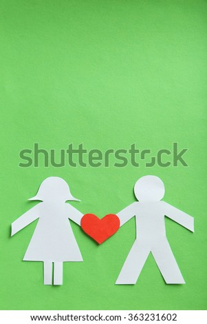 Paper people together in love on the green background - stock photo