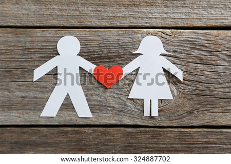 Paper people together in love on the grey wooden background - stock photo