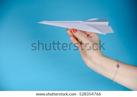 Paper plane in female hand on a blue background