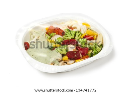 paper plate with prepackaged fast food with plastic foil on top.