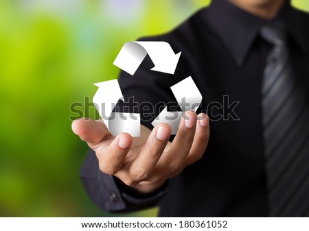 Paper recycle sign in business man hand - stock photo