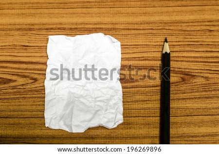 paper scrap with pencil on wood background - stock photo