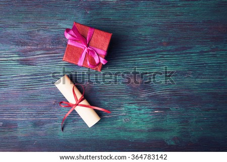 Paper scroll and red gift box on old wooden background - stock photo