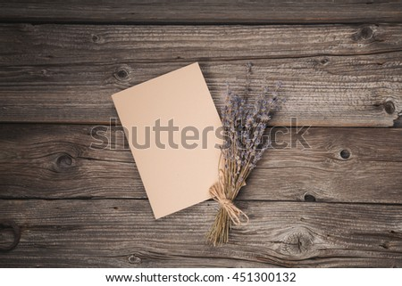 Paper sheet and dried lavender on old wooden background, top view