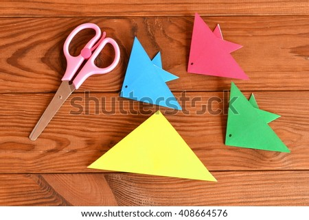 Paper sheets, scissors on a brown wooden table. How to make origami fish - stock photo