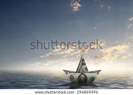 Paper ship floating on water on waves - stock photo