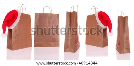 Paper shopping bags with a Christmas hat on white background. - stock photo