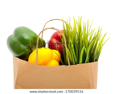 Paper shopping eco bag with green grass,fruit and vegetable isolated over white background. - stock photo