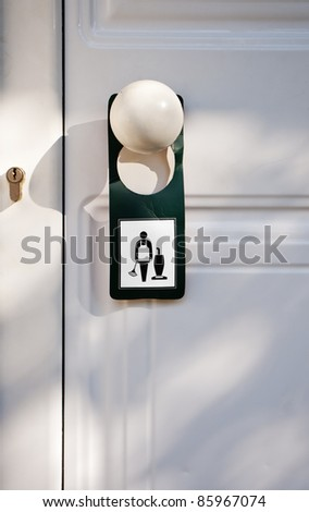 paper symbol sign hung on a white hotel door handle to request housekeeping