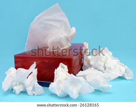 Paper tissue box with used tissues over light blue background - stock photo