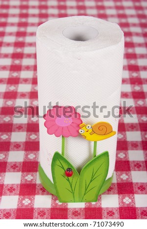 Paper towel in kitchen holder on table - stock photo