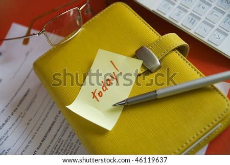 Paper with a reminder on a yellow diary and red background. A reminder that something important you should do today.